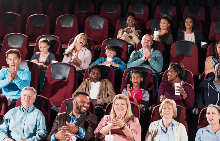 A large, multi-ethnic audience in a movie theater, watching a movie, eating popcorn and drinking soda. The group of people are mixed ages, including children, teenagers, young adults, mid adults and mature men and women, families, friends and couples.